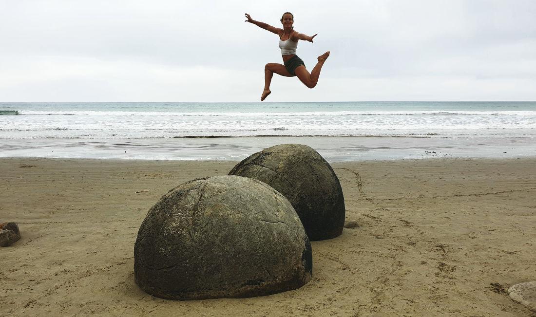 Springende Frau über Steine am Meer
